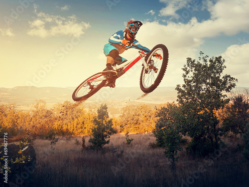 Foto  Man high jump on a mountain bike. Downhill cycling.