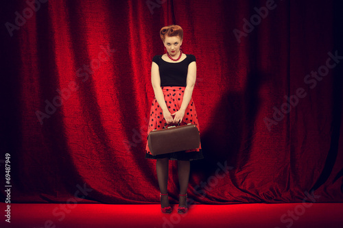 Valokuva  woman  is on the stage  on a background of red curtain.