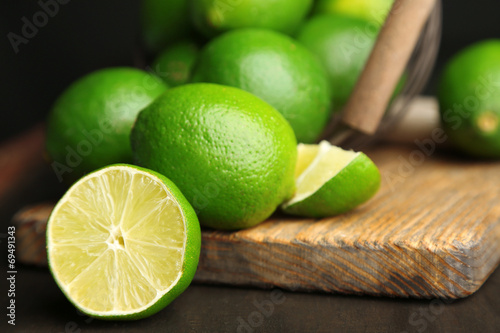 Valokuvatapetti Fresh juicy limes on wooden table, on dark background