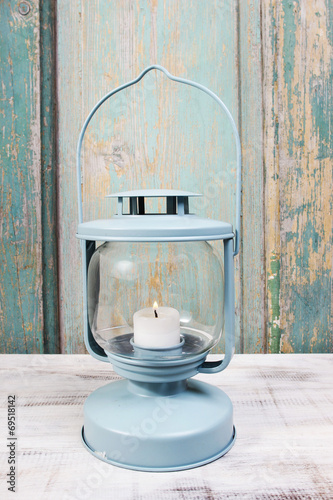 Photo  Iron lantern with white candle inside on wooden table