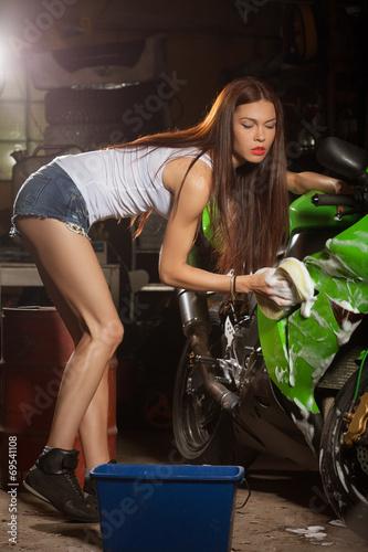 Woman washing motorcycle
