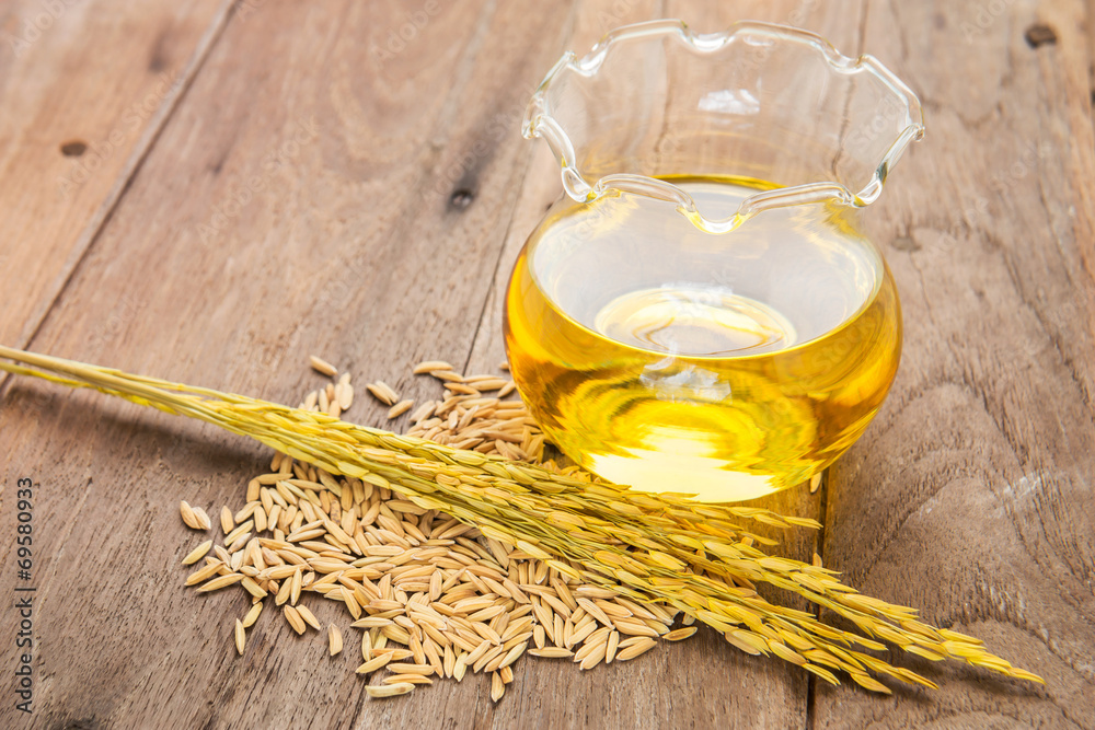 Fototapety, obrazy: Rice bran oil in bottle glass and unmilled rice on wooden backgr