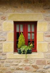 Fototapeta na wymiar Modernes rotes Holzfenster in Natursteinwand aus Granit