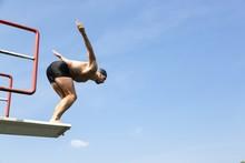 Man Jumping Off Diving Board At Swimming Pool