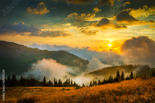 Deurstickers Zwart Amazing mountain landscape with fog and a haystack