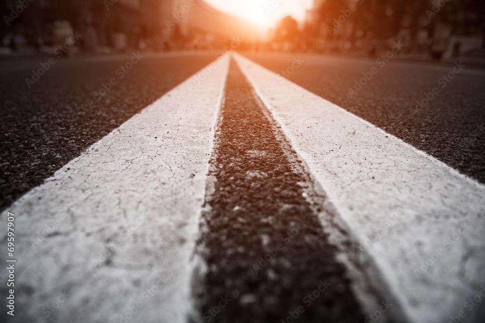 Fototapeta Asphalt city road with white lines ahead and the sunset