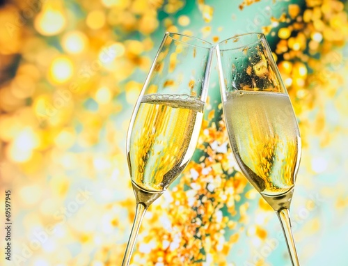 champagne flutes with golden bubbles on golden light background