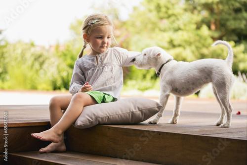 Fotografie, Obraz  Junges Mädchen sitzt draußen auf Holztreppe mit ihrem Hund