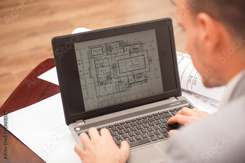 Close-up portrait of laptop with blueprints Canvas Print
