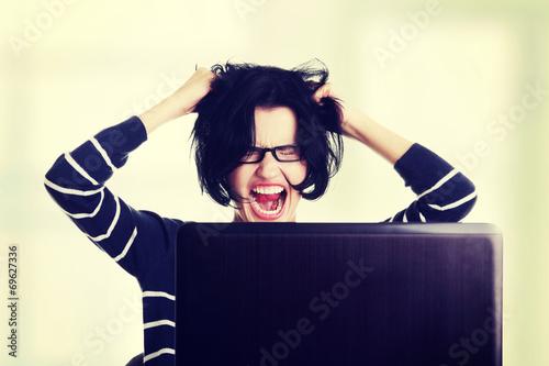 Valokuvatapetti Frustrated woman working on laptop