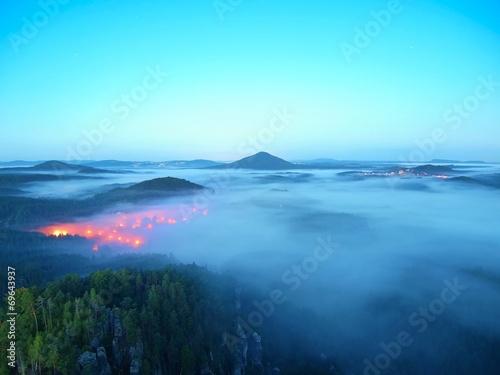 Spoed Foto op Canvas Turkoois Blue misty valley after rainy night, pink orange lights