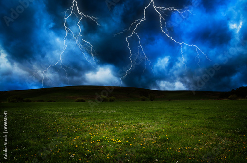 Spoed Fotobehang Onweer Thunderstorm with lightning in green meadow