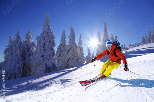 Fotomural  Skier skiing downhill in high mountains against sunset