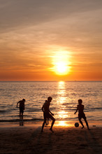 Sunset Beach With Teenagers Playing Football