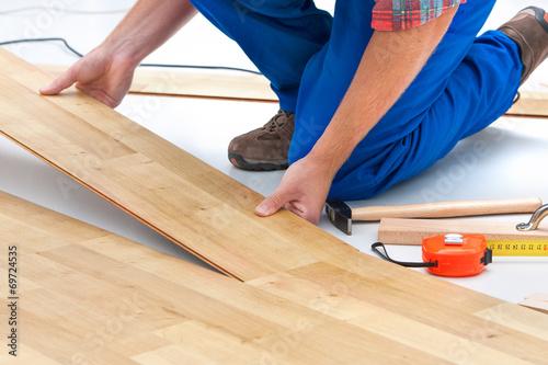 Obraz Man laying laminate flooring - fototapety do salonu