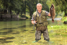 Proud Fisherman Holding Fish In A River