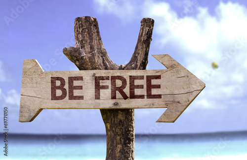 Be Free sign with a beach on background