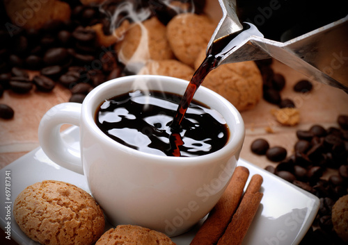 versare il caffè caldo nella tazzina bianca - 69787341