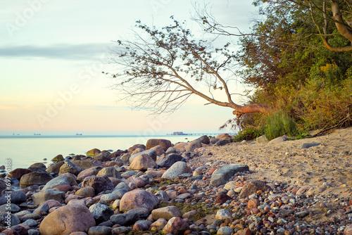 Fotobehang - Morze, kamienista plaża o wschodzie słońca