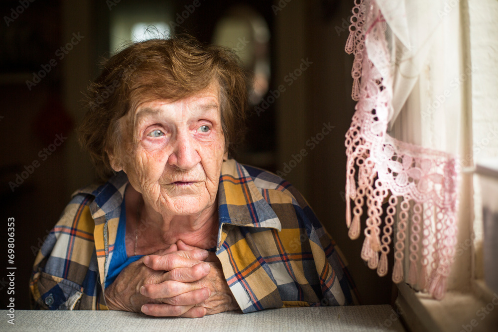 Fototapety, obrazy: Old woman sitting at a table near the window in his house.