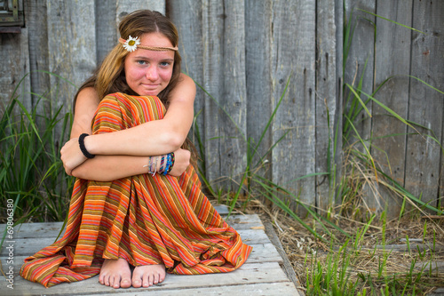 Photo  Young beautiful hippie girl sitting near a house