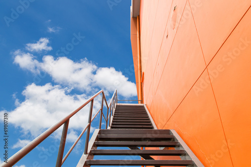 Photo Stands Stairs Metal fire escape or emergency exit on Orange Wall of Buliding
