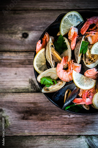 Fotografering Mix of mussels,clams and shrimps on wooden background
