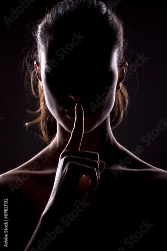 nieznana kobieta z twarzą w cieniu trzymając palec na ustach