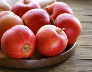Fototapeta na wymiar ripe red apples autumn harvest on a wooden plate
