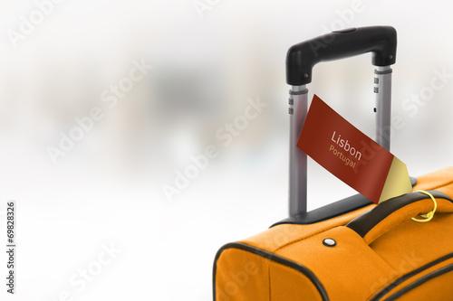 Fotografija  Lisbon, Portugal. Orange suitcase with label at airport.