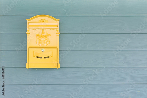 Cuadros en Lienzo Yellow mailbox with green wood background