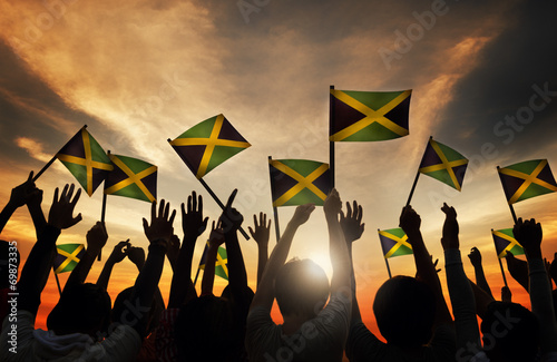 Fotografia, Obraz Group of People Waving Flag of Jamaica in Back Lit