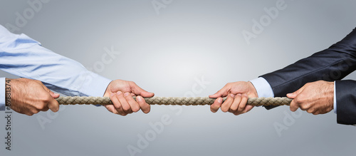 Tela Tug war, two businessman pulling a rope in opposite directions