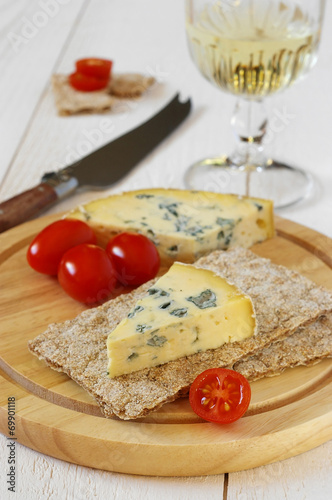 Staande foto Zuivelproducten Tomatoes, blue cheese on crispbread and glass of white wine