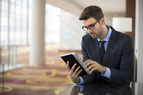 Photo Focused businessman with glasses using tablet at the hotel lobby