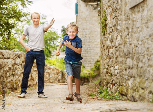 Fotografie, Obraz  Father and running son on old street