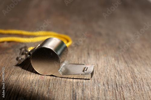 Valokuva  Sport metal whistle on wooden background
