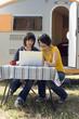 Junges Paar sitzt mit Campingwagen mit Laptop
