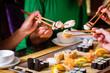 canvas print picture - Junge Leute essen Sushi in Asia Restaurant