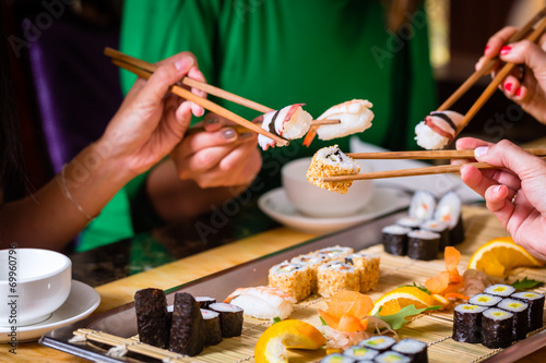 Fototapeta Junge Leute essen Sushi in Asia Restaurant obraz