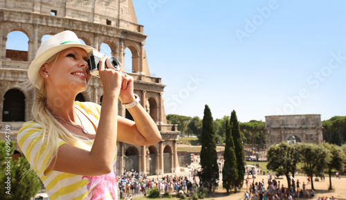 Fotografia  Happy Tourist and Coliseum, Rome. Cheerful Young Blonde Woman