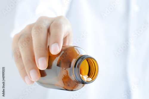 Hand  pouring medicines from the bottle Canvas Print