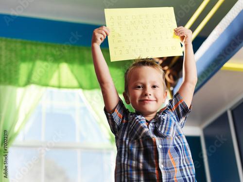 Fotografie, Obraz  proud little boy showing his completed alphabet worksheet