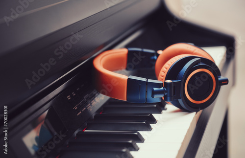 Photo  Blue-orange headphones on a digital piano keyboard
