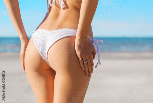 Sexy woman's buttocks in white bikini on the beach Poster