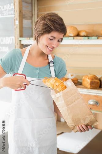 Foto op Plexiglas Bakkerij Pretty waitress putting croissant in paper bag