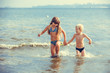 happy little girl and boy in the sea