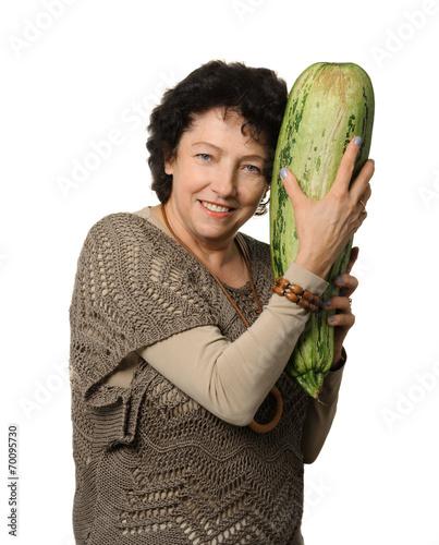 Fényképezés  Woman holding big courgette (zucchini)