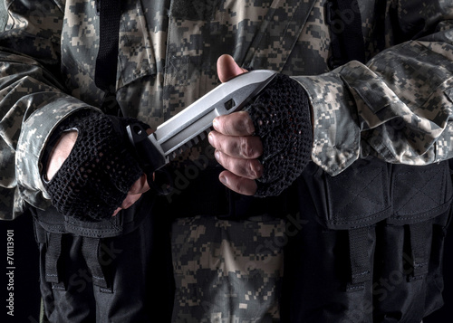Photo  Military man with a knife in a hand on the black background