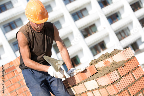 Láminas  Construction bricklayer worker installing brick with trowel